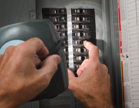 Person using electrical panel, for which Shogun Services provides installation and repair